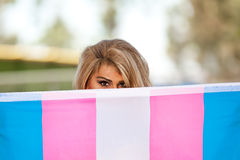 Transgender female with pride flag. Transgender female holding pride flag hiding half her face Royalty Free Stock Photo