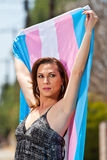Transgender female with pride flag. Transgendered person holding pride flag up and behind her head Stock Photo