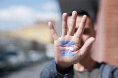 Transgender flag in the palm of the hand. Closeup of the palm of the hand of a young caucasian person with a transgender flag painted in it, in front of his or stock photos