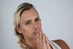 Transgender woman with hands clasped. Against gray background Stock Image