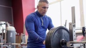 A transição disparou de homem muscular determinado que põe placas pesadas sobre o barbell e que levanta no gym Homem desportivo n video estoque