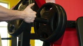 A transição disparou de homem muscular determinado que põe placas pesadas sobre o barbell e que levanta no gym Homem desportivo n filme