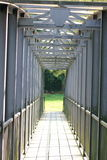 Transition. Narrow iron footbridge in grid design royalty free stock photos