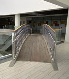 Transition bridge connecting galleries. With a glass parapet, handrails of stainless steel pipes, floor of planks stock photos