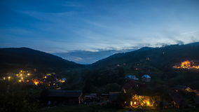 The transition from day to night in the mountains, the movement of the train, the lights of houses stock footage
