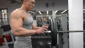 Transition shot of determined muscular man putting heavy plates on barbell and lifting in gym. Young sporty man preparing for weight lifting in a gym. Preparing stock video footage