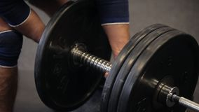 Transition shot of determined muscular man putting heavy plates on barbell and lifting in gym.Young sporty man preparing stock video footage