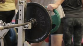 Transition shot of determined muscular man putting heavy plates on barbell and lifting in gym.Young sporty man preparing stock video