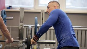 Transition shot of determined muscular man putting heavy plates on barbell and lifting in gym.Young sporty man preparing. For weight lifting in a crossfit gym stock video footage