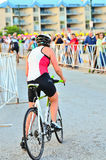 Transition to Bicycle. A female triathlete mounts her bicycle in the transition area during the 2014 Sprint Triathlon in Pewaukee, Wisconsin Royalty Free Stock Images