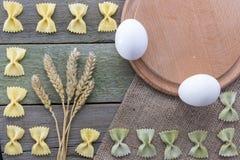 Transitoire de blé, des pâtes, des oeufs et de farine sur un fond en bois, avec l'espace pour le texte Images stock