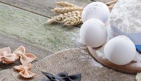 Transitoire de blé, des pâtes, des oeufs et de farine sur un fond en bois, avec l'espace pour le texte Photographie stock