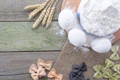 Transitoire de blé, des pâtes, des oeufs et de farine sur un fond en bois, avec l'espace pour le texte Photos stock