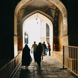 Transitory passageways. from dark to light. Silhouettes of wemen in hijab in light through the gate of Lotfollah Mosque in Ispahan Esfahān.Islamic architecture Stock Photography