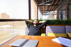 Translator sorting papers and closing laptop lid. European translator sorting papers and closing laptop lid at cafe. Young persistent man dressed in black shirt Royalty Free Stock Photo