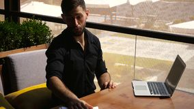 Translator sorting papers and closing laptop lid. European translator sorting papers and closing laptop lid at cafe. Young persistent man dressed in black shirt stock video