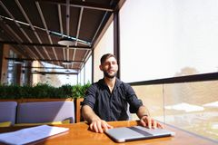 Translator sorting papers and closing laptop lid. European translator sorting papers and closing laptop lid at cafe. Young persistent man dressed in black shirt Stock Photos