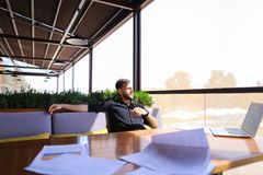 Translator sorting papers and closing laptop lid. European translator sorting papers and closing laptop lid at cafe. Young persistent man dressed in black shirt Royalty Free Stock Photos