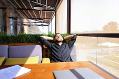 Translator sorting papers and closing laptop lid. European translator sorting papers and closing laptop lid at cafe. Young persistent man dressed in black shirt Royalty Free Stock Image