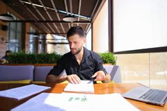 Translator sorting papers and closing laptop lid. European translator sorting papers and closing laptop lid at cafe. Young persistent man dressed in black shirt Stock Photography
