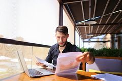 Translator sorting papers and closing laptop lid. European translator sorting papers and closing laptop lid at cafe. Young persistent man dressed in black shirt Stock Photo