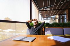 Translator sorting papers and closing laptop lid. European translator sorting papers and closing laptop lid at cafe. Young persistent man dressed in black shirt Stock Image