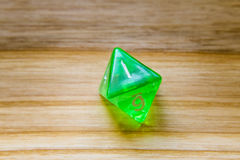 A translucent green eight sided playing dice on a wooden backgro Stock Image