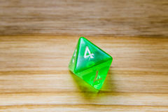 A translucent green eight sided playing dice on a wooden backgro Royalty Free Stock Images