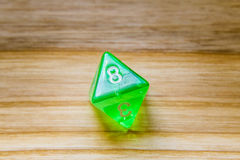 A translucent green eight sided playing dice on a wooden backgro Stock Photos
