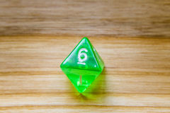 A translucent green eight sided playing dice on a wooden backgro Stock Photography