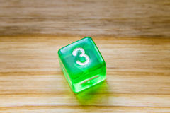 A translucent green six sided playing dice on a wooden backgroun. A beautiful winning playing dice rolled on a side on wooden table Stock Photo