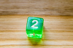 A translucent green six sided playing dice on a wooden backgroun. A beautiful winning playing dice rolled on a side on wooden table Stock Image