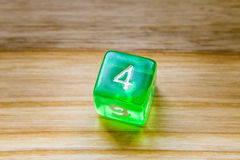 A translucent green six sided playing dice on a wooden backgroun. A beautiful winning playing dice rolled on a side on wooden table Royalty Free Stock Photos