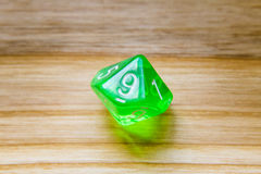 A translucent green ten sided playing dice on a wooden backgroun Stock Photos