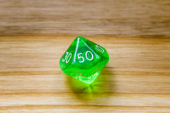 A translucent green ten sided playing dice on a wooden backgroun Stock Images