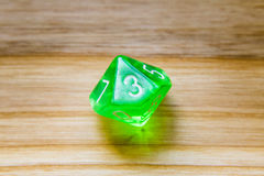 A translucent green ten sided playing dice on a wooden backgroun Royalty Free Stock Photography