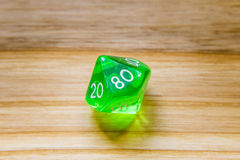 A translucent green ten sided playing dice on a wooden backgroun Royalty Free Stock Photos