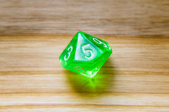 A translucent green ten sided playing dice on a wooden backgroun Stock Image