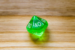A translucent green ten sided playing dice on a wooden backgroun Royalty Free Stock Image