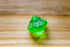 A translucent green ten sided playing dice on a wooden backgroun Royalty Free Stock Images