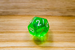 A translucent green twelve sided playing dice on a wooden backgr Royalty Free Stock Image