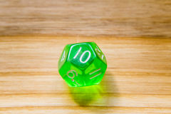 A translucent green twelve sided playing dice on a wooden backgr Royalty Free Stock Photo