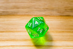 A translucent green twenty sided playing dice on a wooden backgr Royalty Free Stock Photo