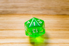 A translucent green twenty sided playing dice on a wooden backgr Stock Photo