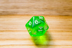 A translucent green twenty sided playing dice on a wooden backgr Royalty Free Stock Image
