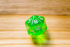 A translucent green twenty sided playing dice on a wooden backgr Royalty Free Stock Photography