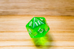 A translucent green twenty sided playing dice on a wooden backgr Stock Photos