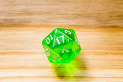 A translucent green twenty sided playing dice on a wooden backgr Stock Image