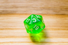 A translucent green twenty sided playing dice on a wooden backgr Stock Photography