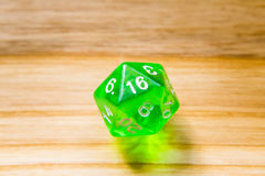 A translucent green twenty sided playing dice on a wooden backgr Royalty Free Stock Photos